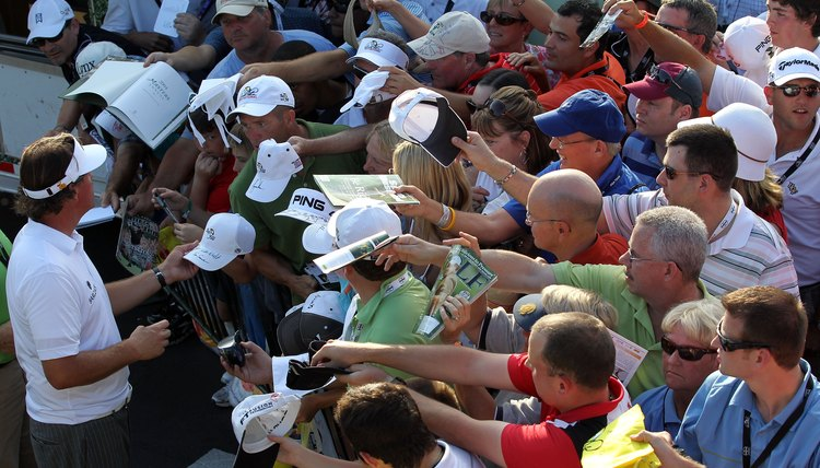 Phil Mickelson, left, signs autographs after playing a round at the 2012 Arnold Palmer Invitational.