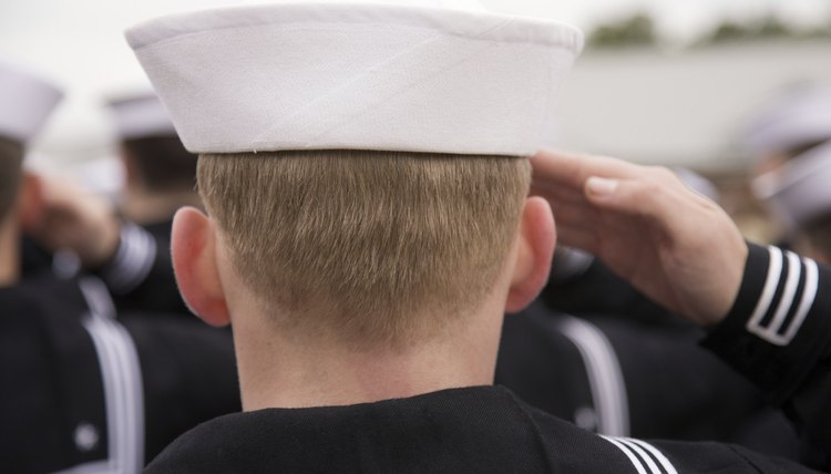 A Navy sailor carries an umbrella in his left hand so his right hand is free to salute.