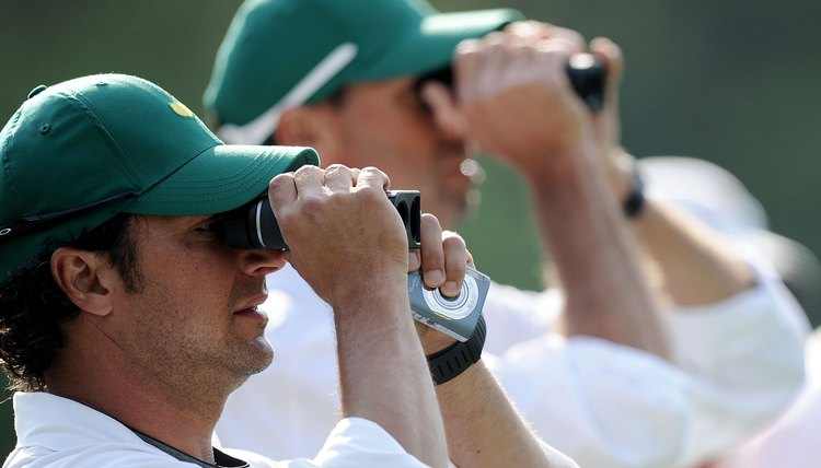 Caddies using rangefinders during a practice round prior to the 2010 Masters.