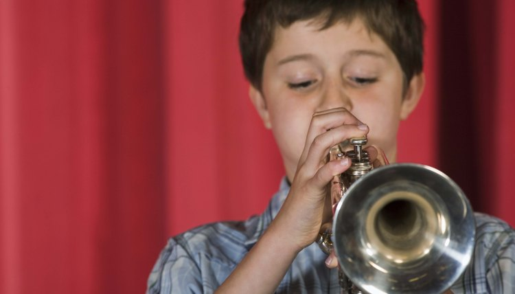 Boy playing trumpet on a stage.
