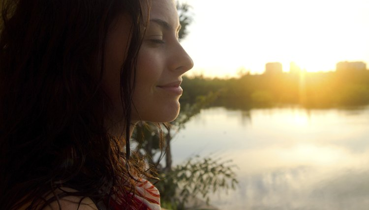 A woman meditating by a city lake in the morning.