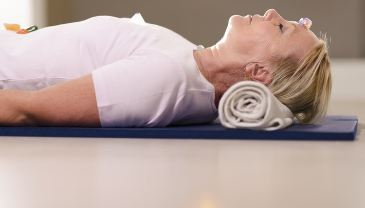 A woman relaxing on a yoga mat with stones resting over her chakras.