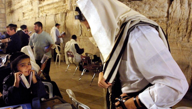 Men don ritual phylacteries at the Wailing Wall.
