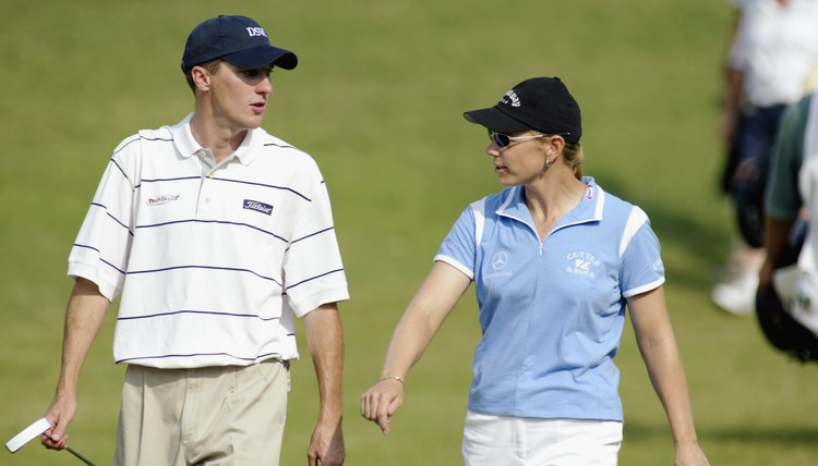Annika Sorenstam walks with playing partner Aaron Barber during the PGA Tour's Colonial tournament in 2003.