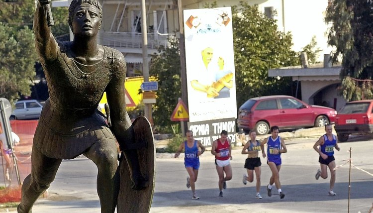 Runners in Greece pass a statue of the Pheidippides in 2002.