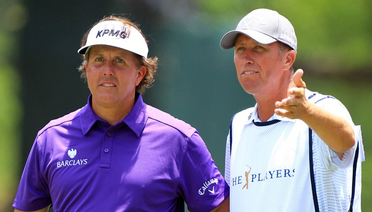 Phil Mickelson and caddie Jim Mackay confer during the 2012 PLAYERS Championship.