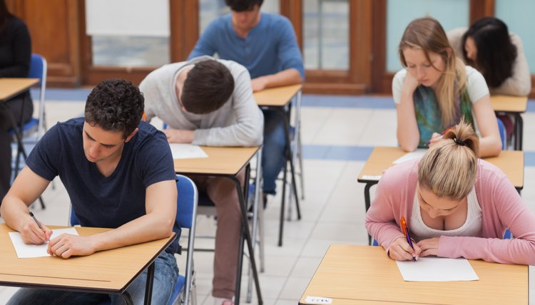 Students taking the ACT test at desks in a highschool.