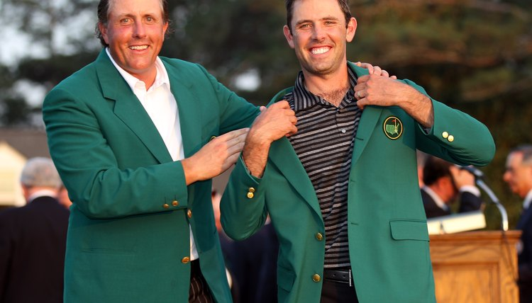 Phil Mickelson (left) presents the traditional green jacket to 2011 Masters champion Charl Schwartzel.