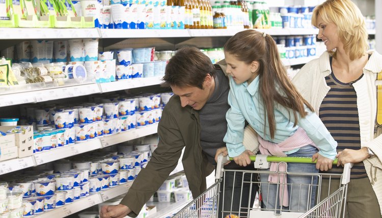 Parents and daughter (8-10) shopping in supermarket, girl standing on trolley