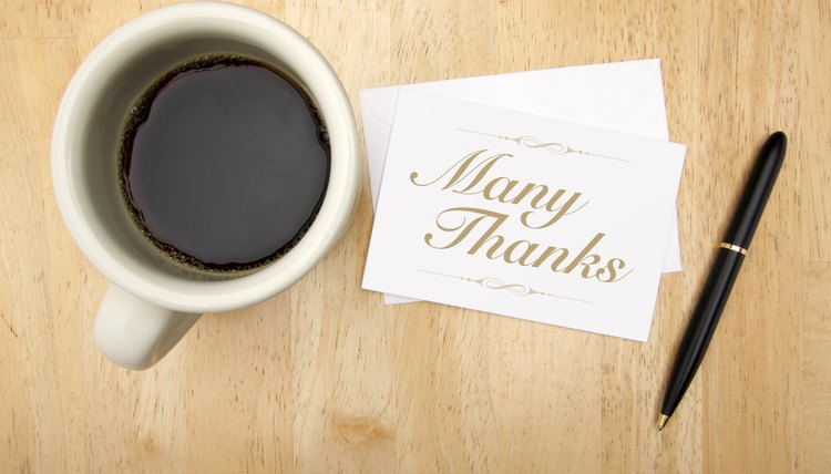 Thank you note and pen next to a cup of coffee