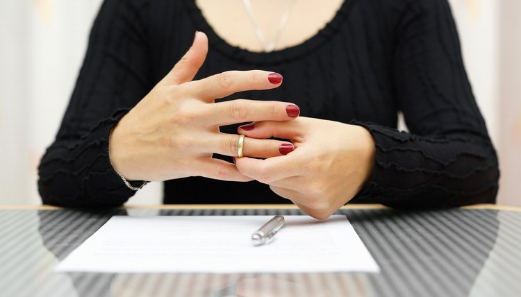 Woman signing dissolution papers and removing wedding ring