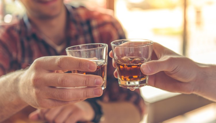 Two friends drinking whiskey shots