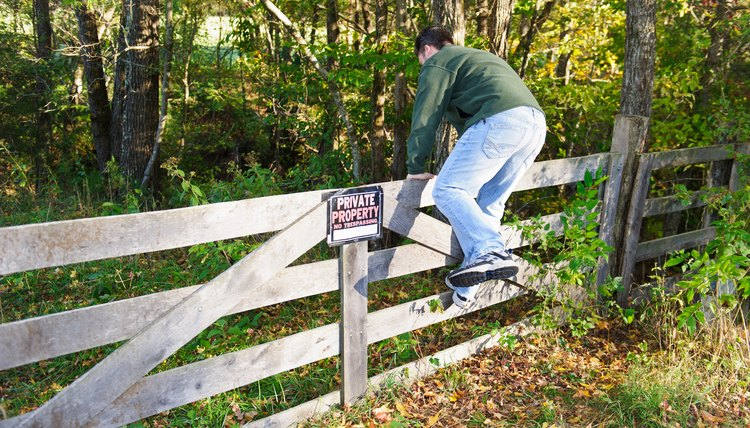 Man climbing fence over Private Property sign