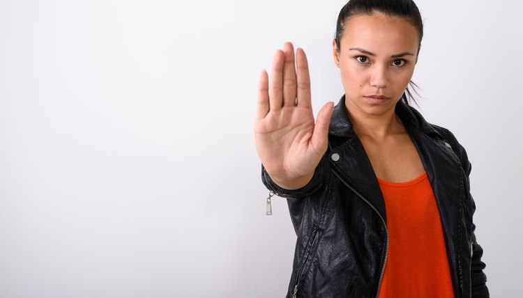 Studio shot of young Asian woman showing stop hand sign while wearing leather jacket against white background