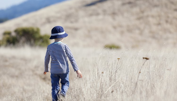 A little boy wearing a hat walking alone in a field