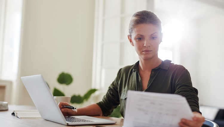 Woman at desk reviewing mortgage and banking paperwork