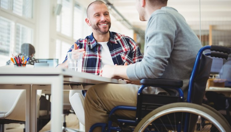 Businessman in wheelchair sitting with colleague in office