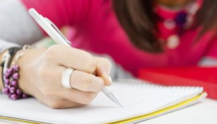 Close-up of girl writing in notebook.