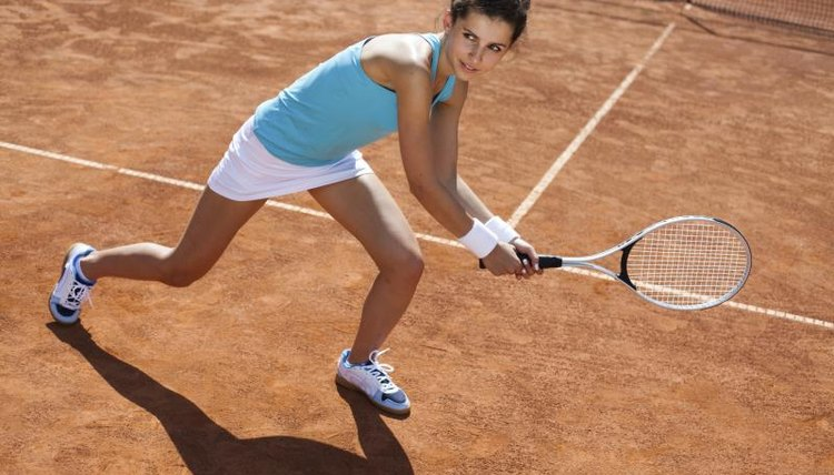 A young woman playing tennis on a clay court.