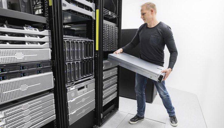 Image of an IT Technician installing a server rack.