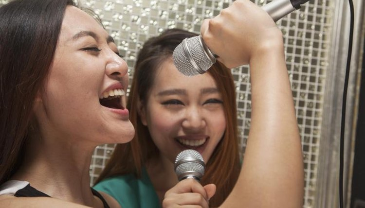 Women singing into microphones