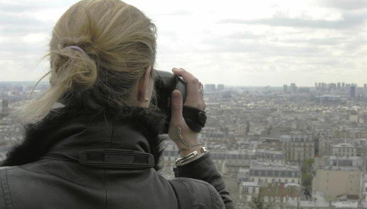 A woman with a camera overlooking the city of Paris.