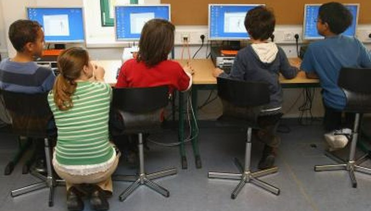 A teacher assists students in a computer lab at school.