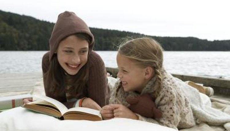 Children reading a book on a lakeside.
