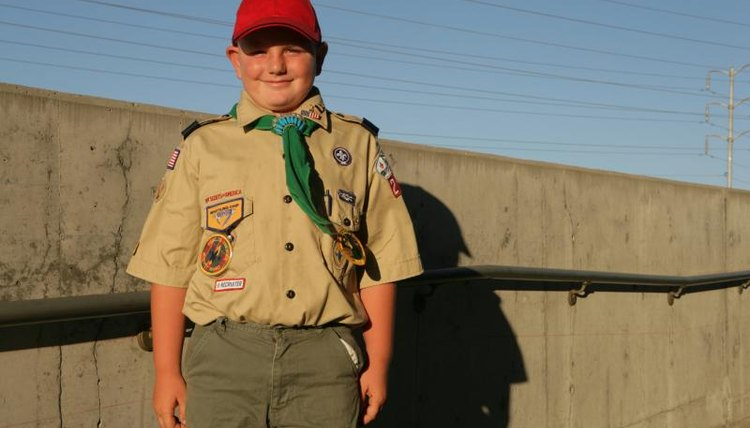 Boy scout standing outside in uniform.