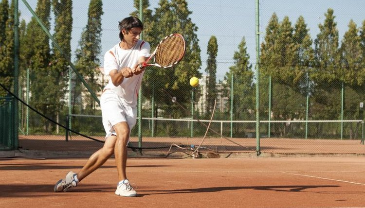 A man taking a backhand swing.
