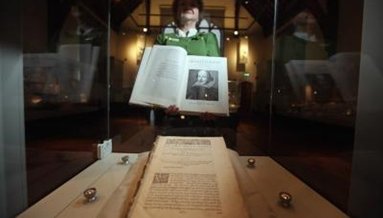 The head of collections at Durham University Library holding a book from the Shakespeare exhibit.
