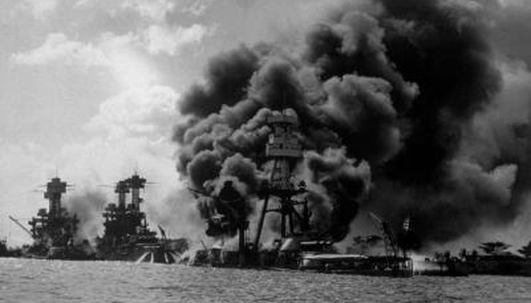 USS Arizona burning in Pearl Harbor during Japanese attack, to the left is the USS Tennessee and USS West Virginia