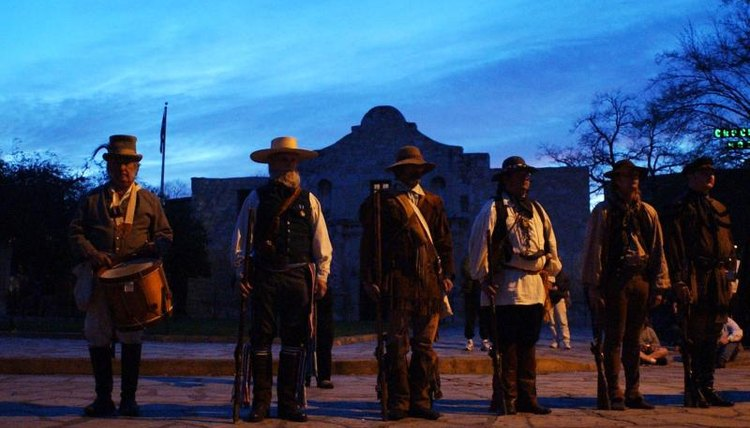 Re-enactors stand in front of the Alamo at dawn