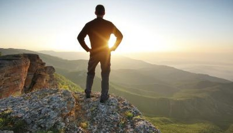 The silhouette of a man viewing a scenic valley from a cliff.