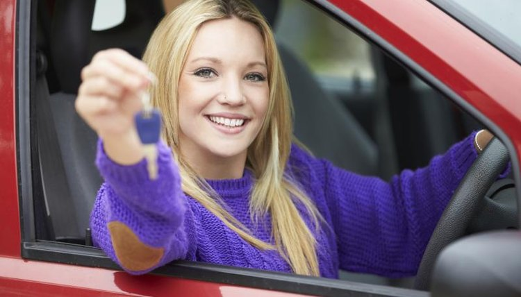 Woman holding keys to a new car.