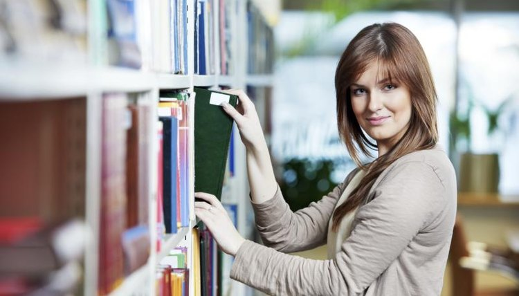 Female student looking through library books