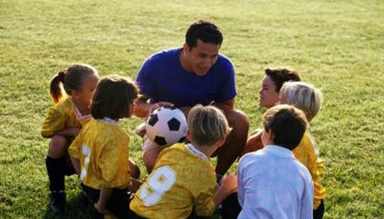 A gym teacher explains the game of soccer to young children on a field.