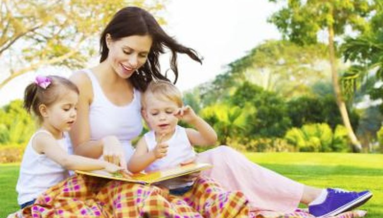 Mother reading outdoors with her two children