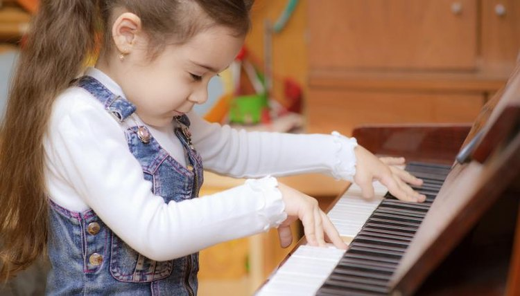 Preschooler playing on small piano.