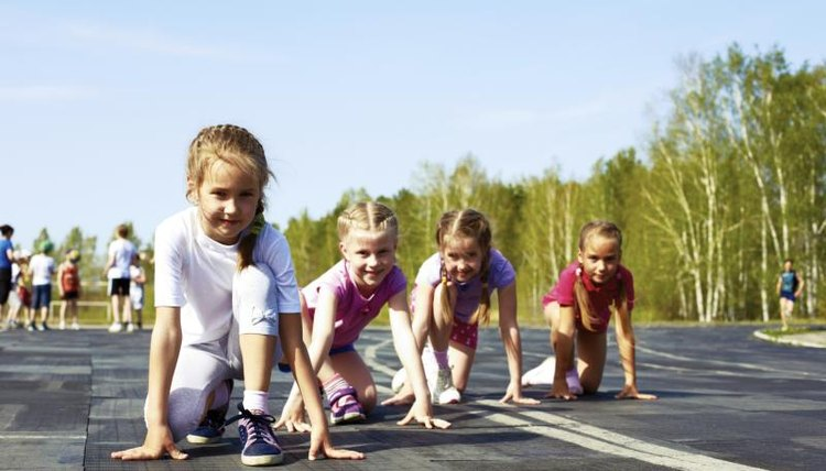 Young kids are lined up to run on a track.