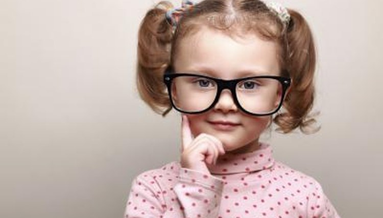 A little girl with pigtails wears glasses and ponders.