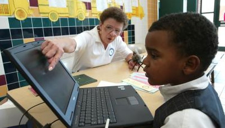 A woman shows a young boy how to use the computer.