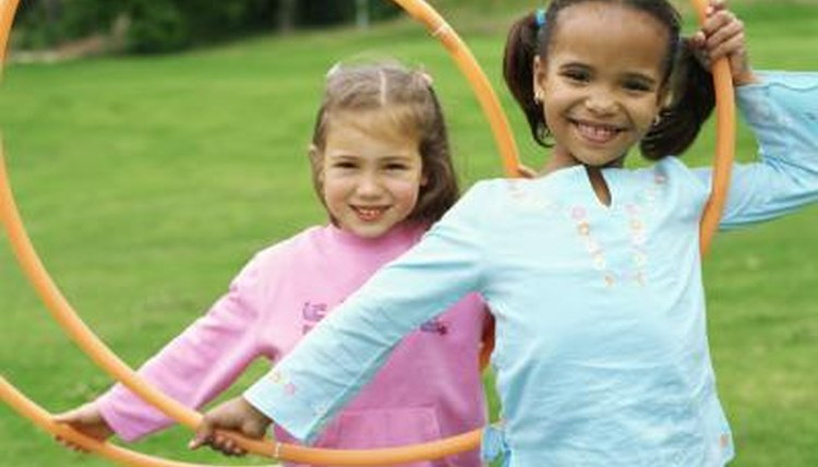 Two young girls holding hula hoops.