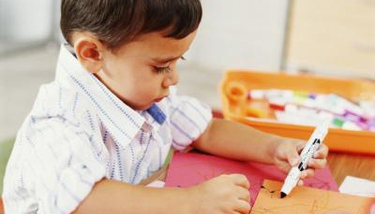Young preschooler drawing at table