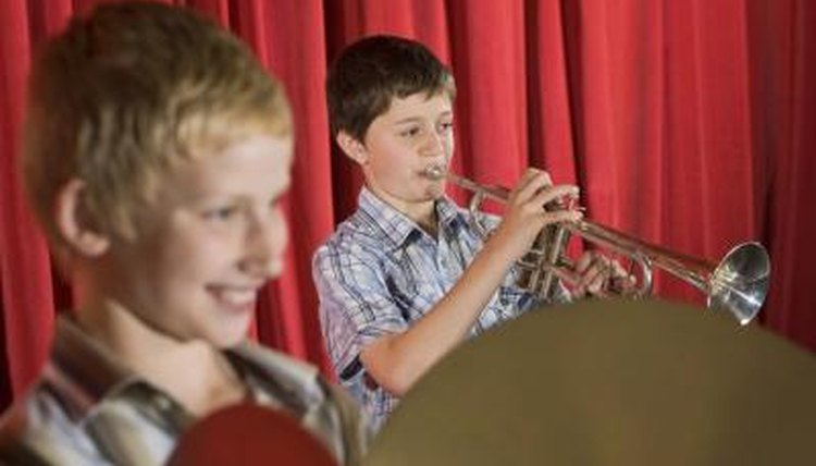 Boys playing instruments at a talent show.