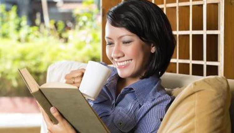Student reading on couch with cup of tea