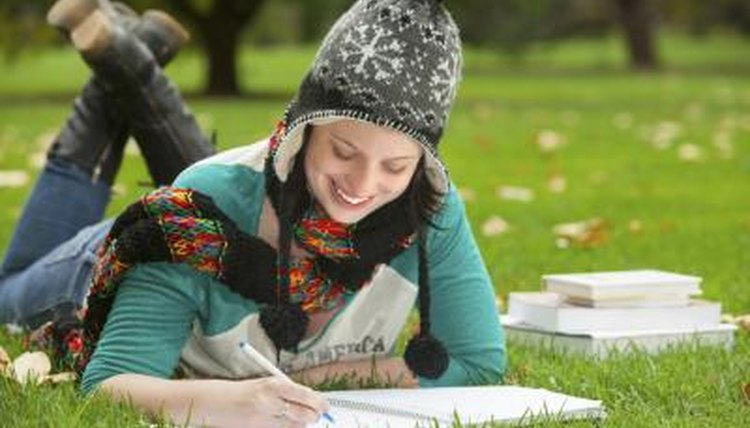 Image of a college student studying on the grass.
