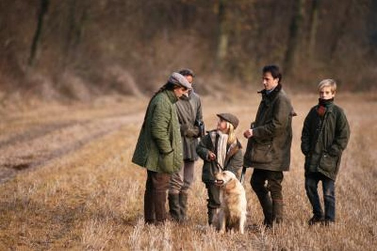 A group o hunters with a dog in the forest.