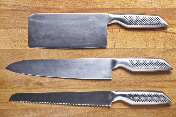 Three stainless steel knives on cutting board.