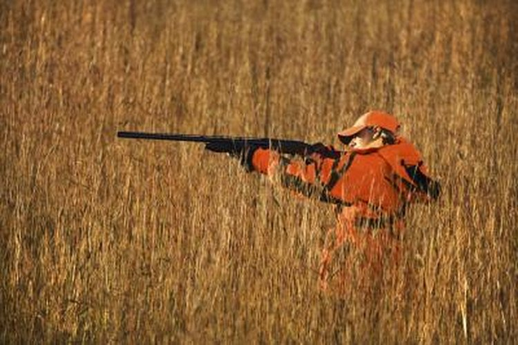 A hunter aiming his rifle in a field of tall grass.